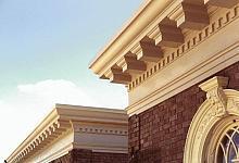 piękna kremowa sztukateria na budynku z ciemnej, brązowej cegły
