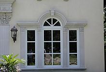 Duże, dekoracyjne okno z efektownym gzymsem, pilastrami, wspornikiem i dekorami.
